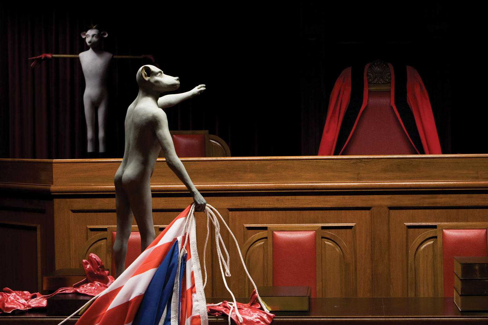 <i>Verity, Faith and Justice</i>, detail: <i>Lamb with stolen boots, Monkey boy</i> (2006). Installation: Courtroom 21 in City Hall for the first Singapore Biennale, 2006. Dimensions set to room. Fiberglass; oil paint; synthetic clay; Dutch and British East India Company flags; used industrial-strength gloves; Singaporean judicial ceremonial robe sewn by a judicial seamstress in Cape Town. Not shown: sculpted figures (<i>Beast</i>, <i>Bird</i>, <i>Custodian</i>, <i>Defendants</i>, <i>Harbinger in correctional uniform</i>, <i>Hobbled ruminant</i>); wood walking sticks; found clothing; prisoner's uniform from pre-democracy South Africa; shackles loaned from Pollsmoor Maximum Security Prison in South Africa. Photograph by Luke Tan