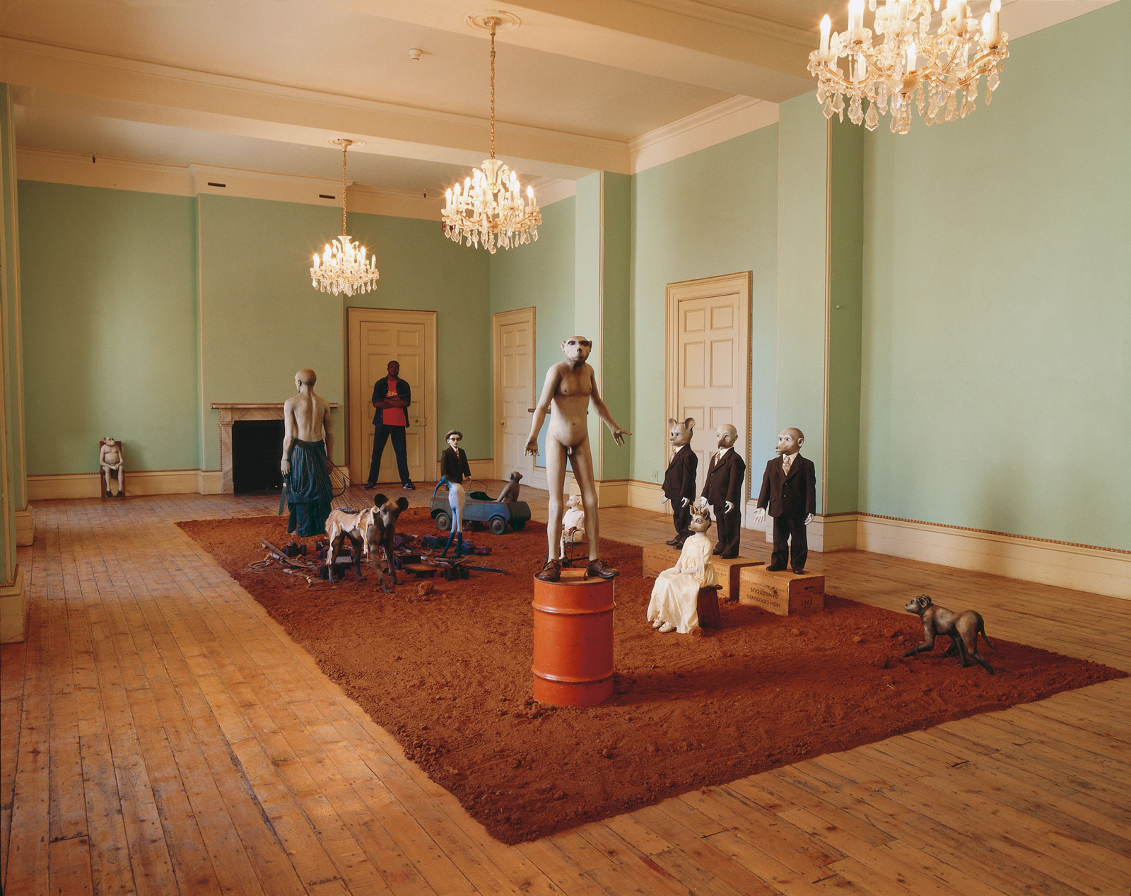 <i>African Adventure</i> (1999–2002). Installation: British Officers' Mess, Castle of Good Hope, Cape Town. Dimensions variable. Sculpted figures (<i>Beast</i>, <i>Custodian</i>, <i>Dog</i>, <i>Doll with industrial-strength gloves</i>, <i>Girl with gold and diamonds</i>, <i>Harbinger</i>, <i>Ibis</i>, <i>Hangman</i>, <i>Radiance of Faith</i>, <i>Settler</i>, <i>Young man</i>); reinforced plaster; oil paint; fiberglass; acrylic paint; synthetic clay; ammunition boxes; found clothing; Venetian gloves; gold; diamonds; jackal skin; machetes; sickles; toy tractors; child's car; child's push chair; oil drum; wood; steel; Bushmanland earth. Photograph by Mark Lewis